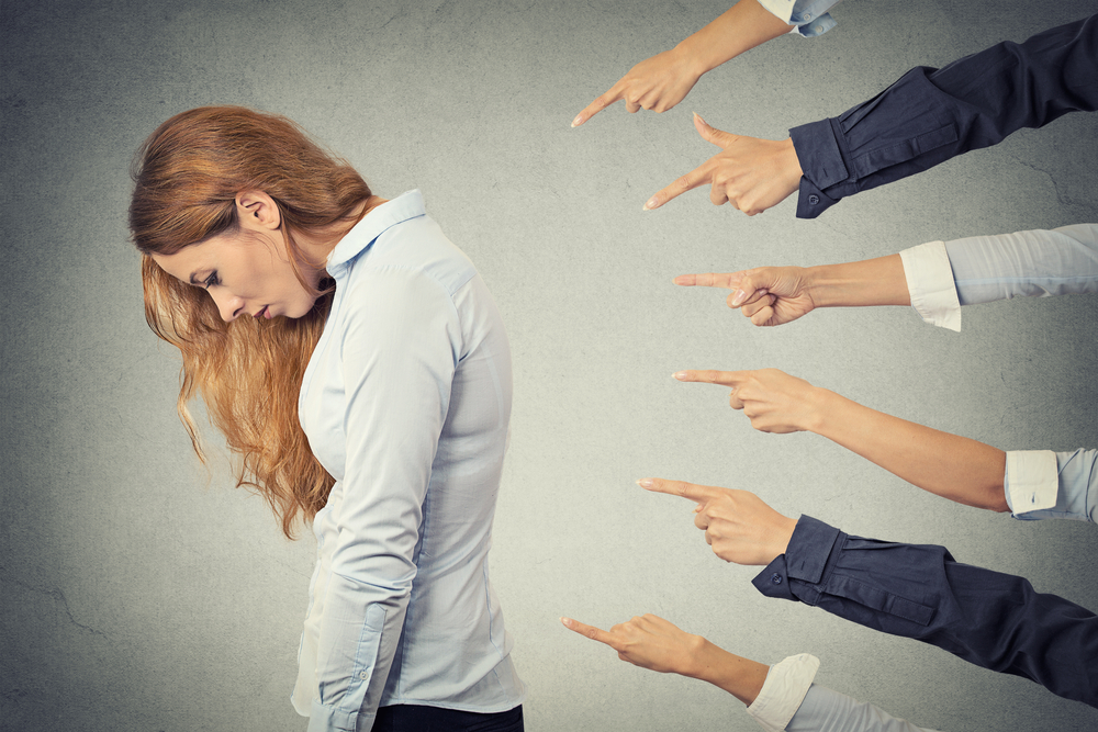 Concept of accusation guilty businesswoman person. Side profile sad upset woman looking down many fingers pointing at her isolated grey office background. Human face expression emotion feeling